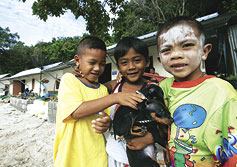 Thai children in front of tsunami relief housing in Phuket, Thailand.